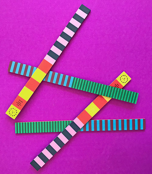 colorful rulers laying on a bright pink background