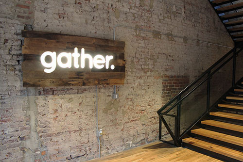 Lighted sign with the word gather. Steps leading off to the right.